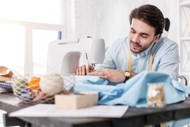 Mi proceso de trabajo. alerta sastre de pelo oscuro sonriendo y trabajando en una máquina de coser