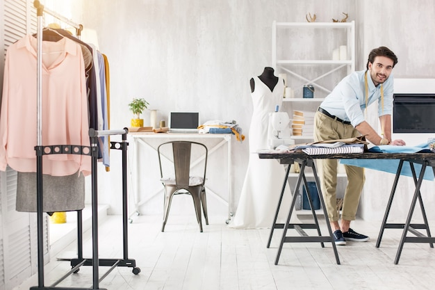 Mi propia oficina. modista experto alegre de pie en la mesa y haciendo un vestido nuevo