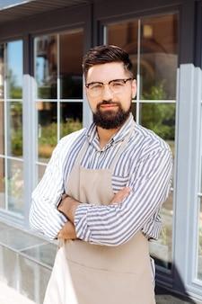 Mi propio negocio. hombre guapo con barba que le mira mientras está de pie con las manos cruzadas frente a su restaurante