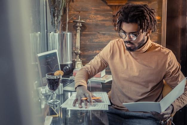 Mi proyecto. persona de sexo masculino barbudo alegre inclinando la cabeza mientras trabaja en su plan de negocios