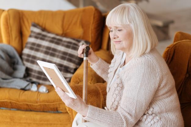 Mi querido esposo. infeliz anciana triste sosteniendo una fotografía y mirándola mientras está de duelo por su marido