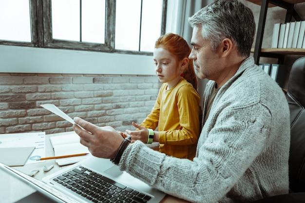 Mi tarea. agradable joven sentada en el regazo de su padre mientras hacía sus deberes con él