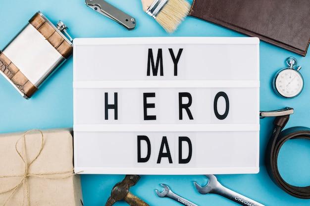 Mi título de papá héroe en tableta cerca de accesorios masculinos