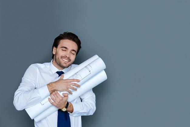 Mi trabajo. agradable hombre positivo encantado sosteniendo su dibujo y sonriendo mientras disfruta de su trabajo