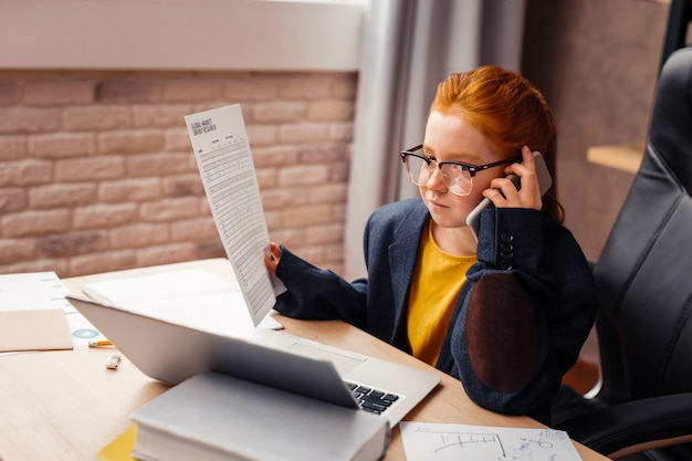Mi trabajo futuro. chica pelirroja inteligente haciendo una llamada telefónica mientras sostiene un documento en la mano