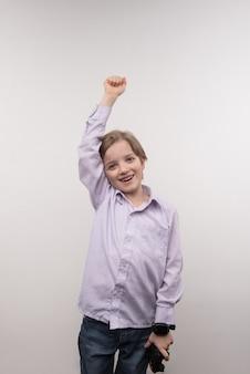 Mi victoria. niño feliz alegre sosteniendo su mano mientras gana el juego