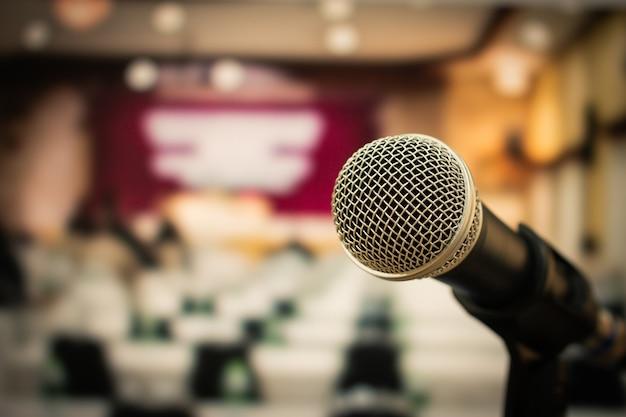 Micrófono en abstracto borrosa de discurso en sala de seminario o hablando de luz de pasillo de conferencia