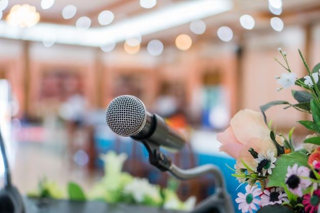 Micrófono en abstracto difuminado del habla en la sala de seminarios o en la luz de la sala de conferencias en el escenario