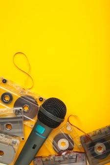 Micrófono y cassette sobre fondo amarillo con espacio de copia