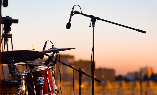 Un micrófono cerca de una batería en el escenario.