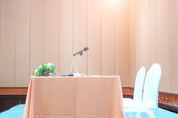 Micrófono cerca de un disparo en una sala de reuniones o seminarios con personas desenfocadas para el espacio de copia