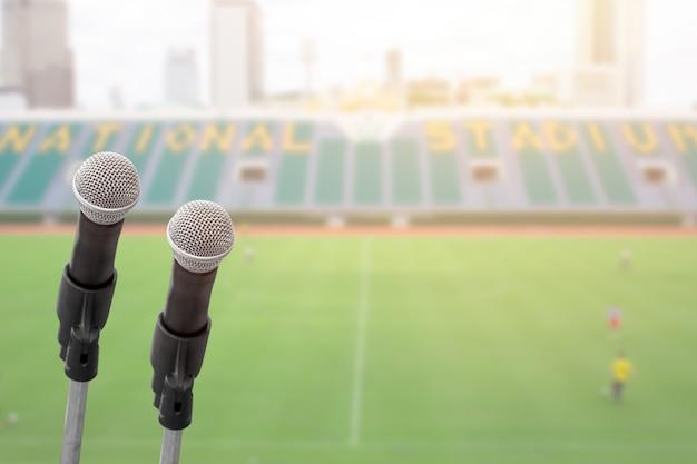 Micrófono para comentarista con estadio deportivo de fútbol con espacio para texto