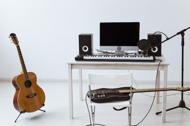 Micrófono, computadora y equipo musical, guitarras y piano de fondo. estudio de grabación casero