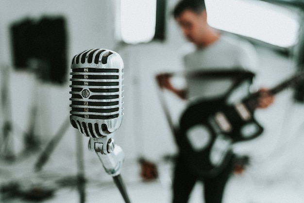 Micrófono de condensador de diafragma grande con un músico sosteniendo una guitarra eléctrica en el fondo