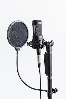 Micrófono de condensador profesional con filtro pop en un estudio.