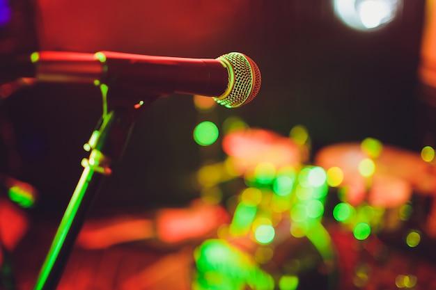 Micrófono contra desenfoque en bebidas en pub y restaurante de fondo.