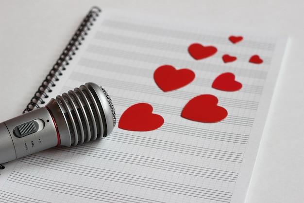 Micrófono y corazones rojos de papel se encuentran en un cuaderno de música limpio.