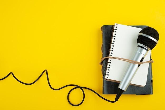 Micrófono y cuaderno abierto vacío sobre papel amarillo