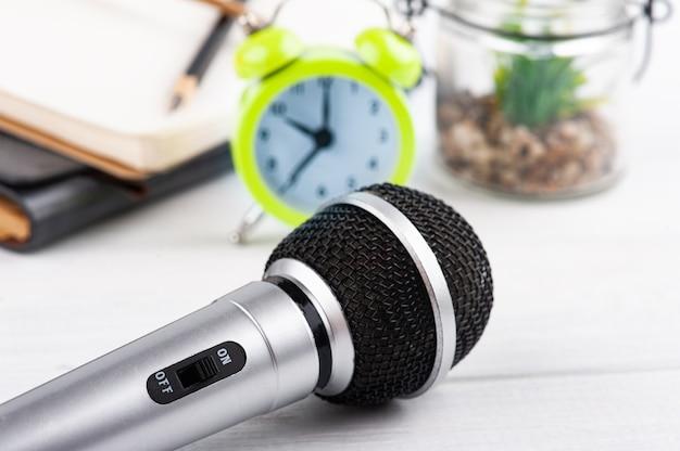 Micrófono y despertador, cuaderno de madera blanca