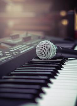 Micrófono en el teclado de la música con fondo borroso de la marca de música