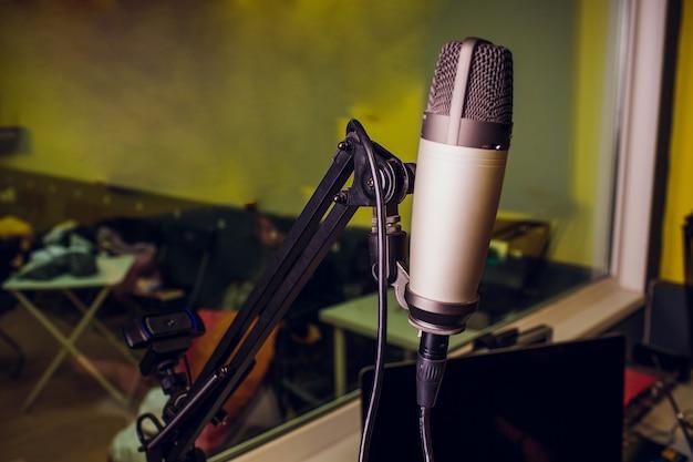 Micrófono en el escenario de la comedia con rayos reflectores, imagen de alto contraste