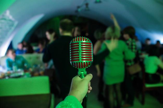 El micrófono está en el escenario de una discoteca. cantante sostiene y canta en el micrófono