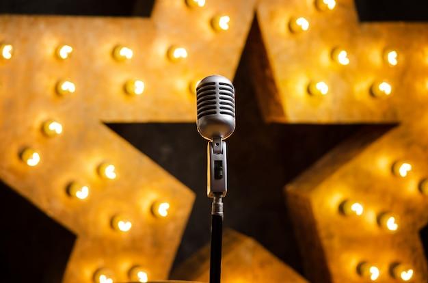 Micrófono en el escenario del teatro o karaoke, estrella luminosa dorada en el fondo