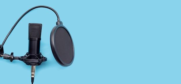 Micrófono de estudio sobre fondo azul.