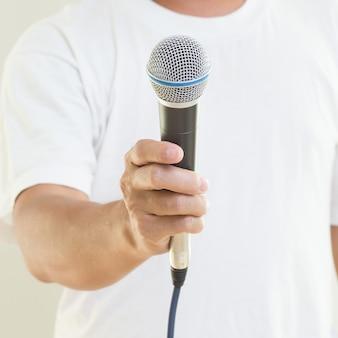 Micrófono de explotación de mano de hombre