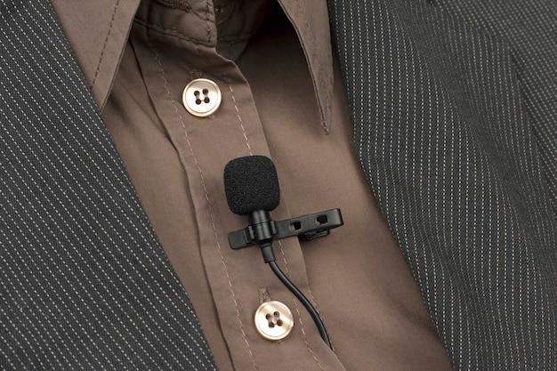 El micrófono lavalier con clip se adjunta al primer plano de la ropa de las mujeres. grabación de audio del sonido de la voz en un micrófono de condensador.