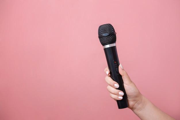 Micrófono en mano femenina en pared rosa foto de stock