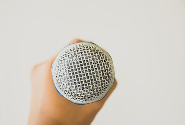 Micrófono de mano sobre fondo gris.