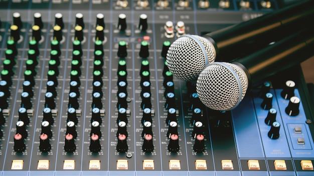 Micrófono con mezclador de sonido en lugar de trabajo de estudio para grabación de sonido y medios en vivo.