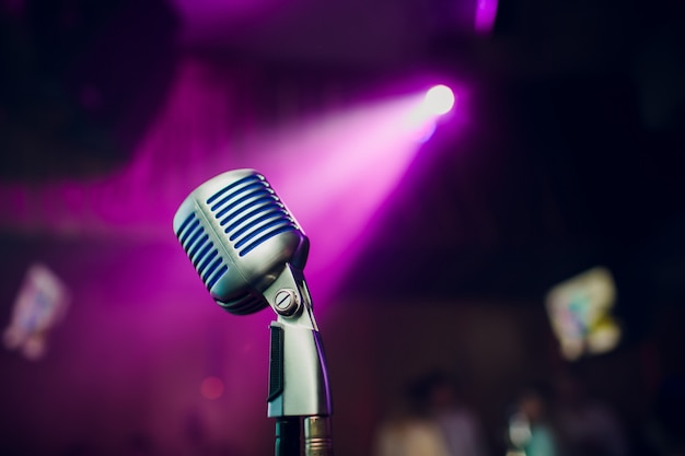 Micrófono moderno para cantar contra un hermoso bokeh de colores borrosos.