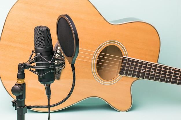 Micrófono moderno y guitarra de seis cuerdas.