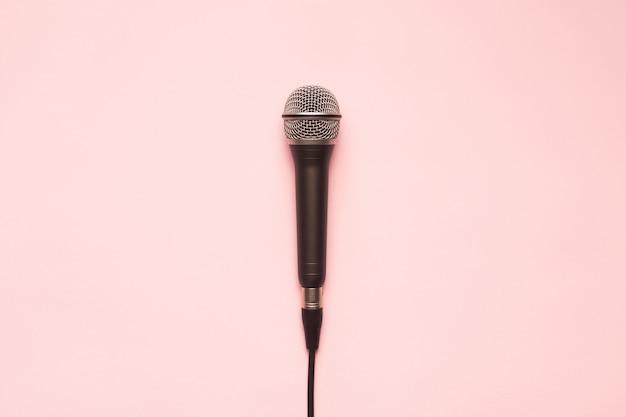 Micrófono negro y plateado sobre un fondo rosa