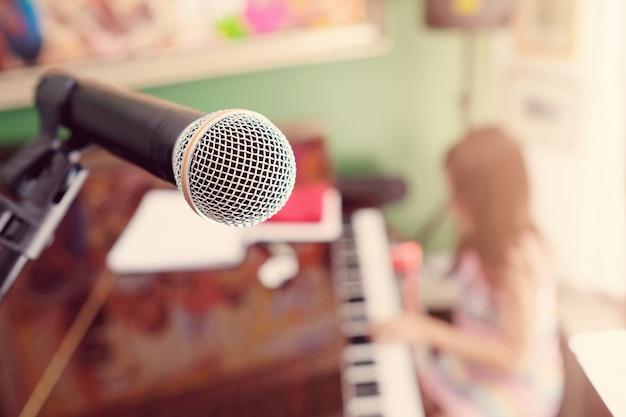 Micrófono con niña borrosa tocando el piano