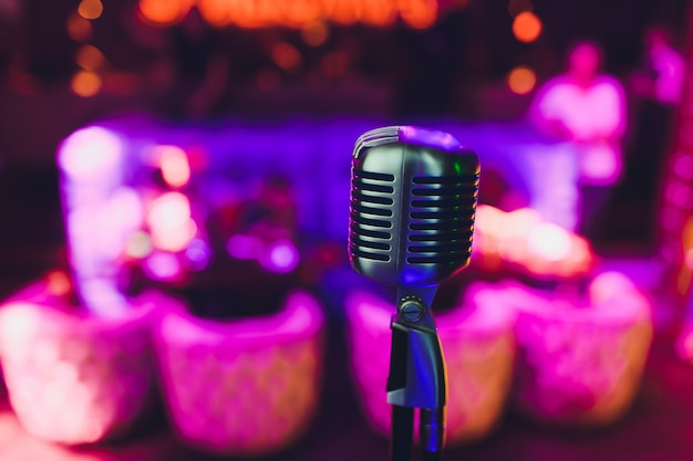 Micrófono retro contra desenfoque de fondo de restaurante de luz colorida.