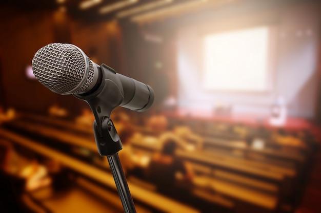 Micrófono sobre el foro empresarial borroso reunión