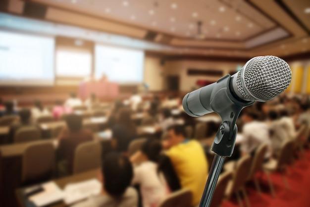 Micrófono sobre el foro de gente de negocios borrosa reunión conferencia formación aprendizaje coaching concepto, fondo borroso.