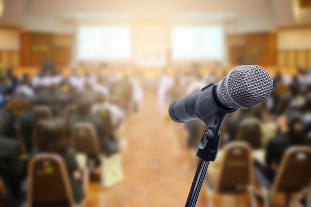 Micrófono sobre el foro de gente de negocios borrosa