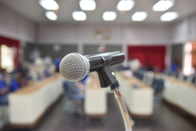 Micrófono sobre la foto borrosa abstracta de la sala de conferencias o seminarios en el centro de exposiciones