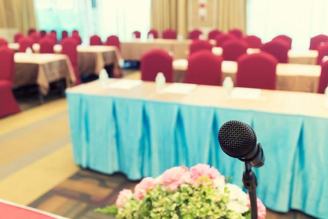 Micrófono sobre la foto borrosa abstracta de la sala de conferencias o seminario con backgrou asistentes