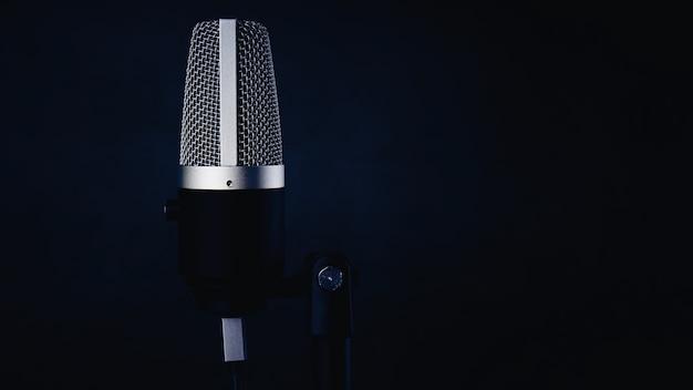 Micrófono único sobre fondo de pared azul oscuro