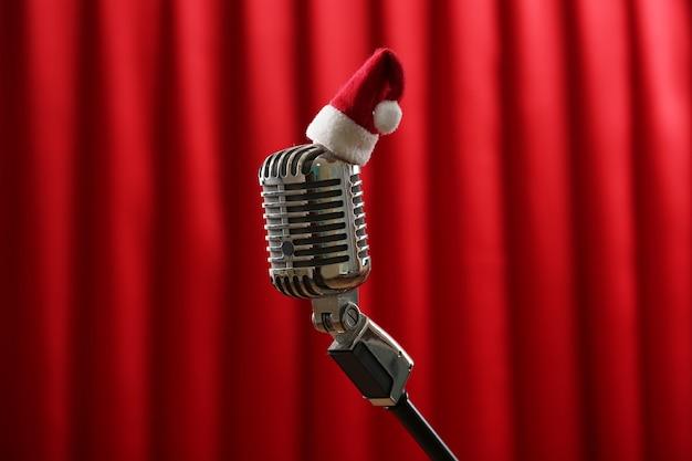Micrófono vintage con gorro de navidad en cortina roja