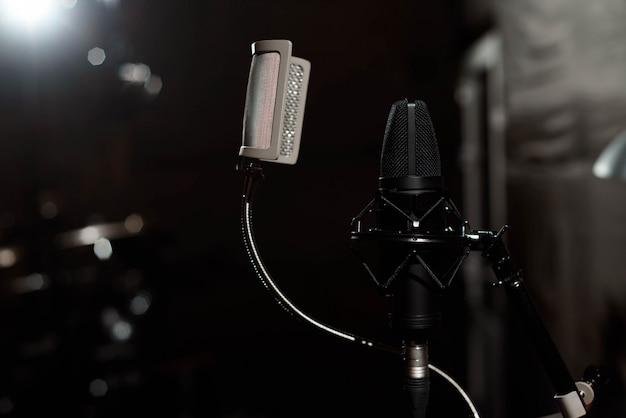 Micrófono vocal negro está parado en la sala de estudio de grabación de sonido