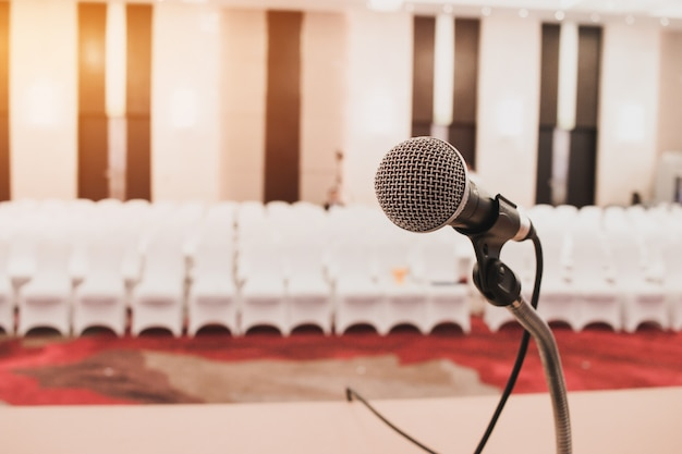 Micrófonos en abstracto difuminado del habla en la sala de seminarios o en la sala de conferencias que habla al frente