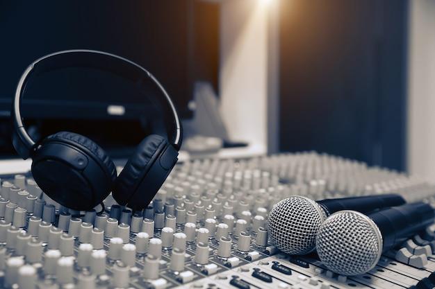 Micrófonos y auriculares con mezclador de sonido en estudio.