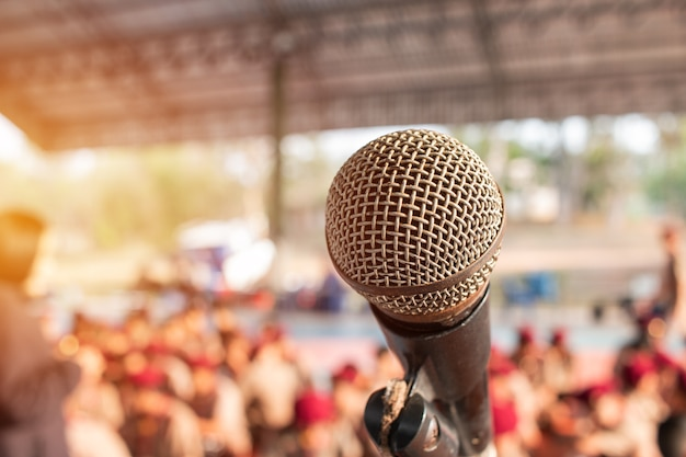 Micrófonos viejos en stand en resumen borrosa de discurso en campo de scout hablando luz para pr