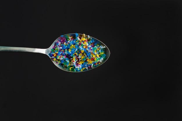 Microplástico de color en cuchara sobre fondo negro